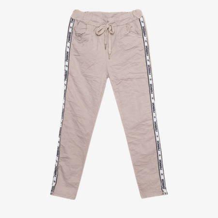 Beżowe spodnie dresowe z lampasami - Odzież